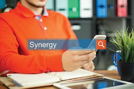 concurrence: Young man using smartphone and searching SYNERGY word on internet Stock Photo