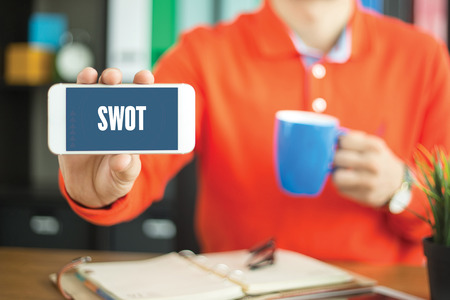 Young man showing smartphone and SWOT word concept on screen