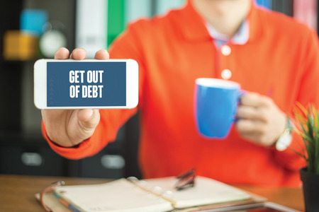 Young man showing smartphone and GET OUT OF DEBT word concept on screen