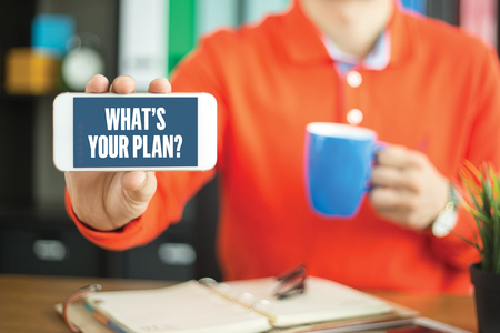 business ideas: Young man showing smartphone and WHATS YOUR PLAN? word concept on screen Stock Photo