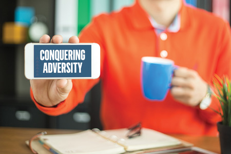 adversity: Young man showing smartphone and CONQUERING ADVERSITY word concept on screen