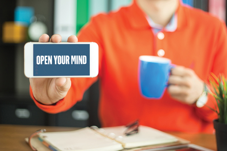 Young man showing smartphone and OPEN YOUR MIND word concept on screen