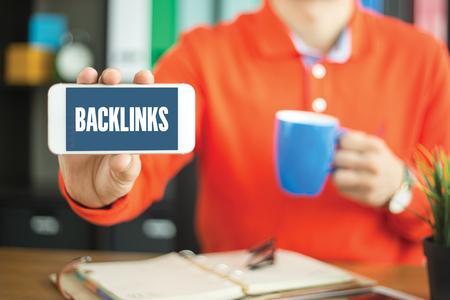 Jonge mens die smartphone en BACKLINKS woordconcept op het scherm tonen Stockfoto