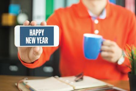 Young man showing smartphone and HAPPY NEW YEAR word concept on screen