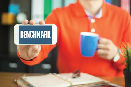 benchmark: Young man showing smartphone and BENCHMARK word concept on screen Stock Photo