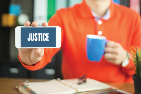 Young man showing smartphone and JUSTICE word concept on screen Stock Photo