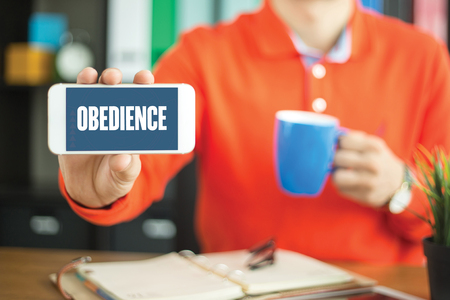 obediencia: Young man showing smartphone and OBEDIENCE word concept on screen