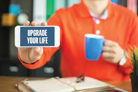 life extension: Young man showing smartphone and UPGRADE YOUR LIFE word concept on screen Stock Photo