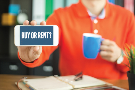 Young man showing smartphone and BUY OR RENT? word concept on screen