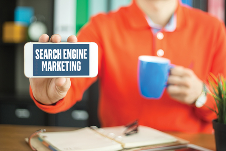 webmaster: Young man showing smartphone and SEARCH ENGINE MARKETING word concept on screen