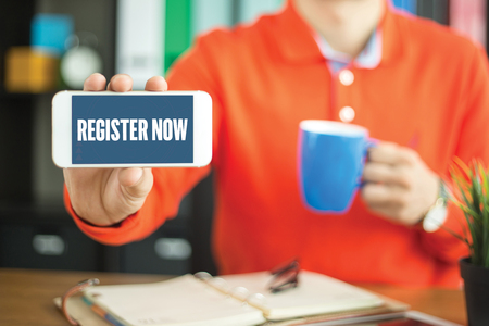 subscribing: Young man showing smartphone and REGISTER NOW word concept on screen