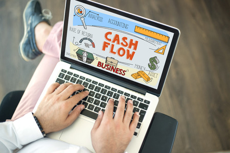 People using laptop and CASH FLOW concept on screen