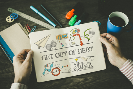 trouble free: GET OUT OF DEBT sketch on notebook Stock Photo