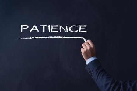 paciencia: Empresario por escrito en la pizarra PACIENCIA Foto de archivo