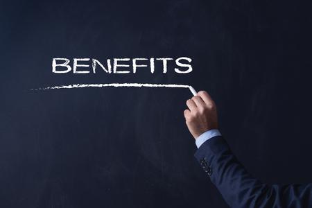 privilege: Businessman writing BENEFITS on Blackboard