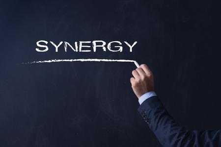 sinergia: Empresario por escrito en la pizarra SYNERGY