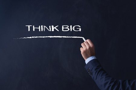 surpassing: Businessman writing THINK BIG on Blackboard