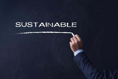 sustain: Businessman writing SUSTAINABLE on Blackboard Stock Photo