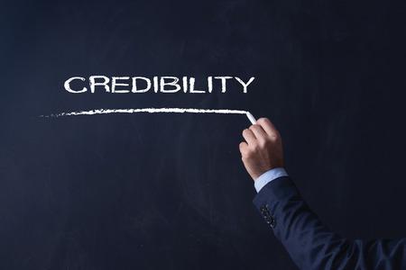credibility: Businessman writing CREDIBILITY on Blackboard