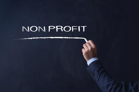 non profit: Businessman writing NON PROFIT on Blackboard