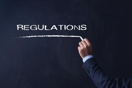 regulate: Businessman writing REGULATIONS on Blackboard Stock Photo