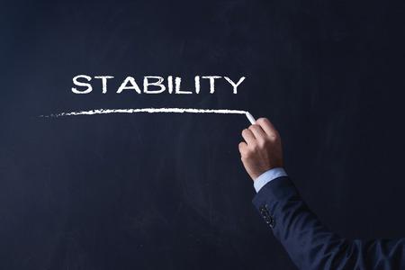 Businessman writing STABILITY on Blackboard Stock Photo