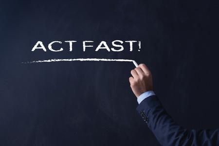 act: Businessman writing ACT FAST! on Blackboard Stock Photo