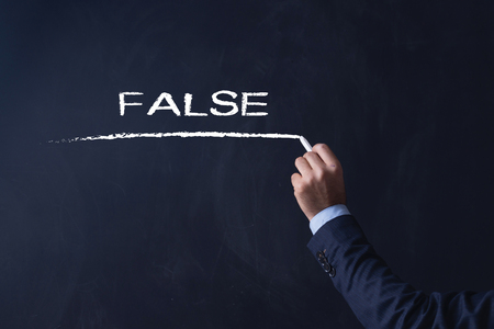 untrue: Businessman writing False on Blackboard Stock Photo