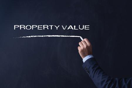 Businessman writing PROPERTY VALUE on Blackboard