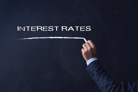 interest: Businessman writing INTEREST RATES on Blackboard Stock Photo