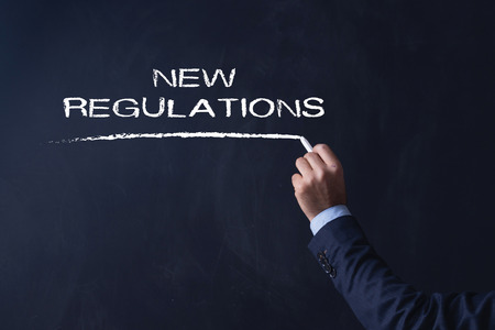 compliant: Businessman writing NEW REGULATIONS on Blackboard Stock Photo