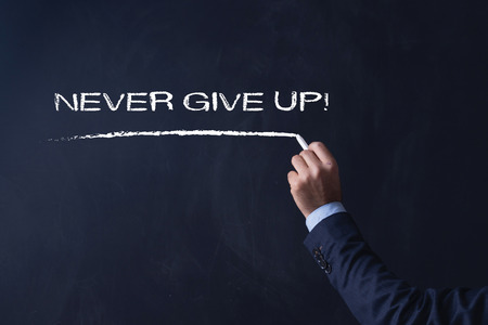 not give: Businessman writing NEVER GIVE UP! on Blackboard