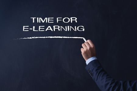 instances: Businessman writing TIME FOR E-LEARNING on Blackboard Stock Photo