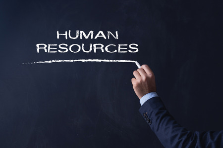 Businessman writing HUMAN RESOURCES on Blackboard Stock Photo