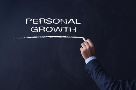 superacion personal: Empresario por escrito en la pizarra CRECIMIENTO PERSONAL