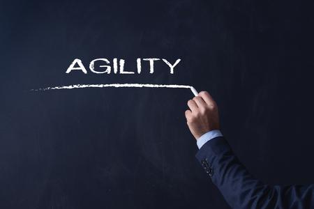 agility: Businessman writing AGILITY on Blackboard