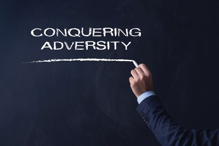 adversity: Businessman writing CONQUERING ADVERSITY on Blackboard Stock Photo