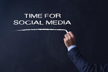 Businessman writing TIME FOR SOCIAL MEDIA on Blackboard