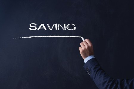 frugality: Businessman writing SAVING on Blackboard