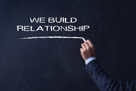 social grace: Businessman writing WE BUILD RELATIONSHIP on Blackboard