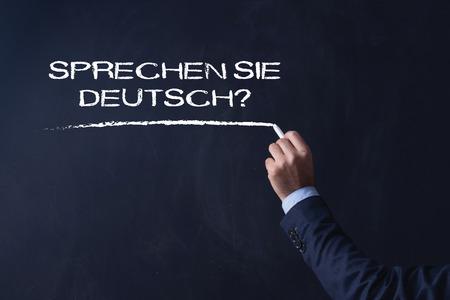 deutsch: Businessman writing SPRECHEN SIE DEUTSCH? on Blackboard
