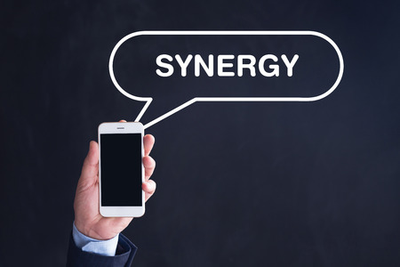 concurrence: Hand Holding Smartphone with SYNERGY written speech bubble