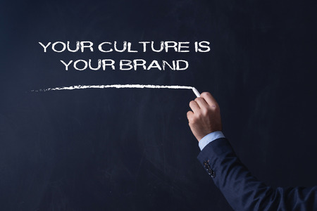 community recognition: Businessman writing YOUR CULTURE IS YOUR BRAND on Blackboard