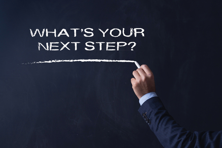 what's ahead: Businessman writing WHATS YOUR NEXT STEP? on Blackboard Stock Photo