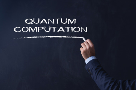 computation: Businessman writing QUANTUM COMPUTATION on Blackboard
