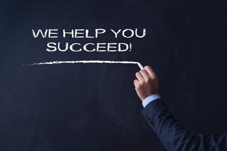 succeed: Businessman writing WE HELP YOU SUCCEED! on Blackboard