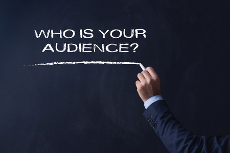 preference: Businessman writing WHO IS YOUR AUDIENCE? on Blackboard