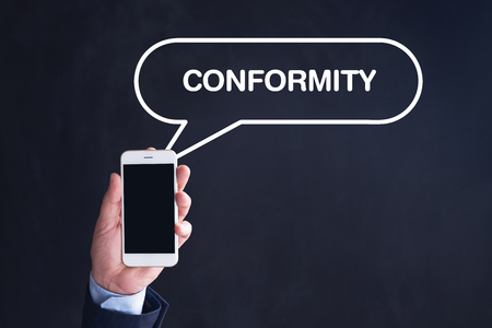conformity: Hand Holding Smartphone with CONFORMITY written speech bubble Stock Photo