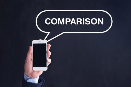 comparison: Hand Holding Smartphone with COMPARISON written speech bubble Stock Photo