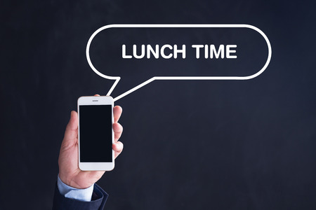 take time out: Hand Holding Smartphone with LUNCH TIME written speech bubble